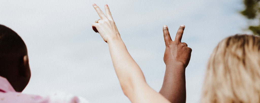Two arms raised with peace fingers